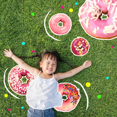Kid lying on grass with donuts